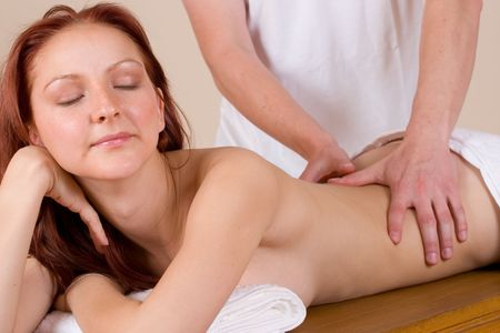 acupressure hands: Woman lying on massage table with the hands of male masseuse on her back and shoulders - Eyes Closed Stock Photo