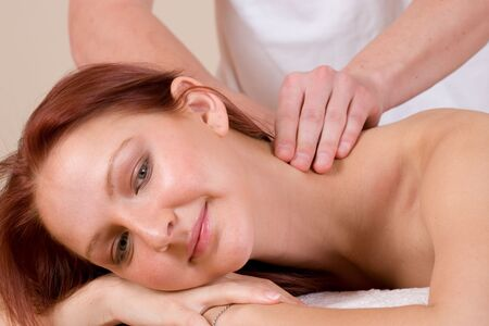 indulgent: Woman lying on massage table with the hands of male masseuse on her back and shoulders