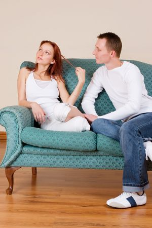 Woman and boyfriend sitting on couch, talking photo