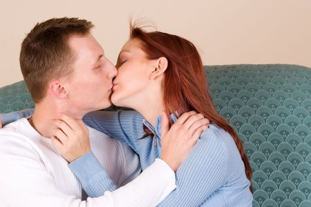 Woman and boyfriend kissing on couch photo