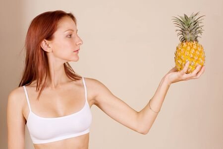 Woman holding a pineapple photo