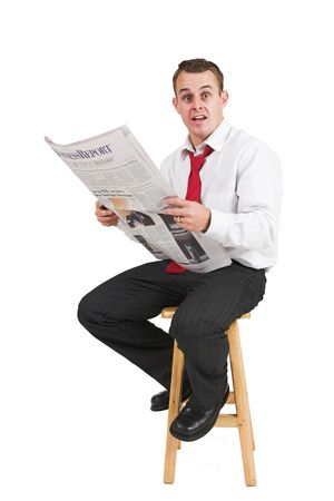 Businessman in black trousers, white shirt and red tie. Reading newspaper