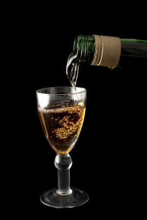 Wine is being poured into a glass - black background photo