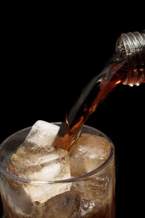 Cooldrink is being poured into a glass full of ice, black background - copy space Stock Photo - 266582