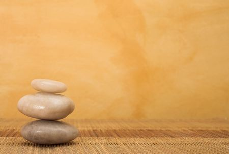 hot stone massaging stones on bamboo cloth in front of wall - copy space Stock Photo - 266563