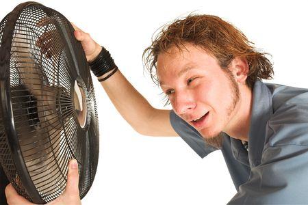 transpiration: Man shirt bleu avec refroidissement devant un ventilateur.
