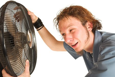 Man with blue shirt cooling down in front of a fan. Stock Photo