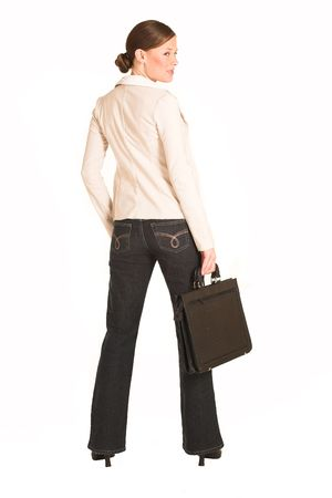 Business woman dressed in jeans and a beige jacket.  Holding a leather suitcase photo