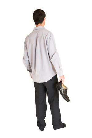 mascular: Businessman standing in socks, holding shoes in one hand.