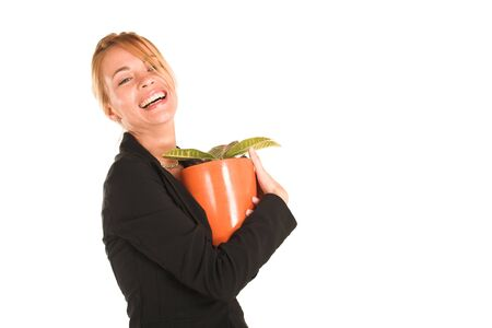 Blonde business lady in formal black suit.  Holding a potplant and laughing - Copy Space