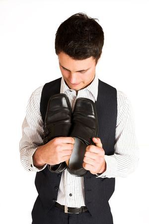 mascular: Businessman holding his shoes.  Looking down at shoes.