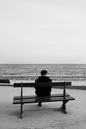 horison: Man on Bench, next to the sea - High Key, Black and White