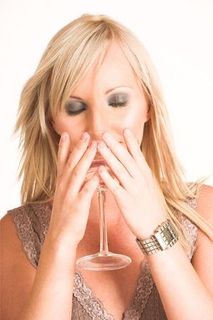 Blond business woman dressed in a beige top.  Drinking out of a martini glass - eyes closed photo