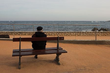 Man on Bench, next to the sea photo