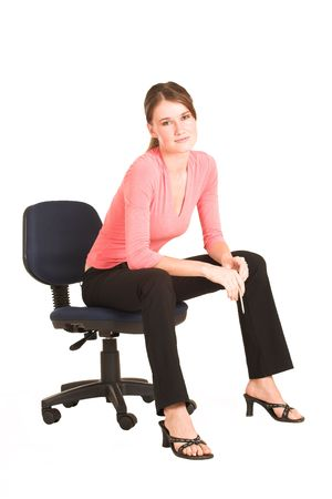 informal: Brunette business woman in  an informal light pink shirt.  Sitting on an office chair.