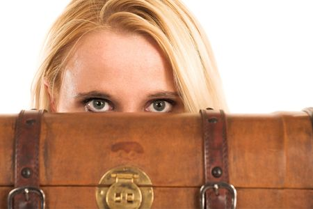 Blond business woman. Peeking over an old suitcase photo