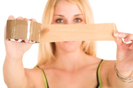 informal: Blonde business lady in an informal green top. Holding a piece of tape.  Shallow DOF - hands and tape in focus, face out of focus.