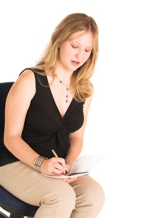 down sitting: Pregnant Business Woman, looking down, sitting down on office chair wearing black top and beige pants, writing on notepad
