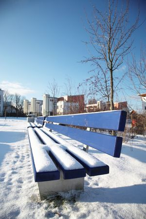 Bench covered in snow in a park in Munch. photo