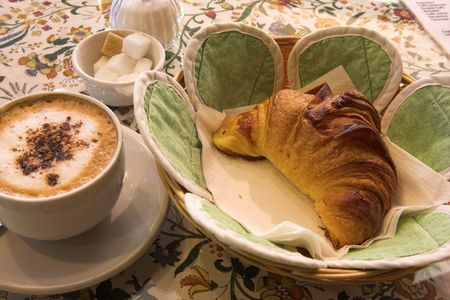 Coffee and Croissant in a French Patisserie - Focus on Croissant photo