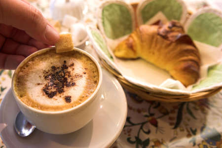 Coffee and Croissant in a French Patisserie. Mans hand holding sugar cube - Focus on Coffee photo