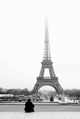 A person sitting, looking at the Eiffel Tower in Paris, France.  Black and white.  Copy space. Stock Photo - 376901