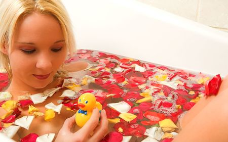 woman in a bath, holding a plastic toy duck. photo