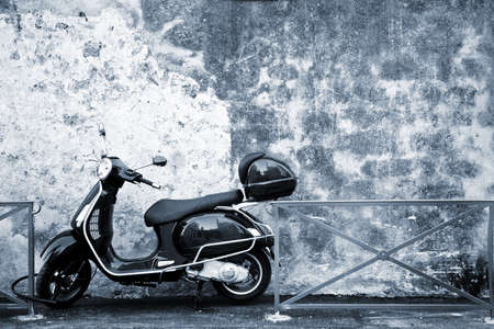 helmet seat: Scooter in front of a wall.   Blue tone. Copy space.