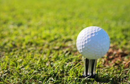 A close-up of a golf ball on a golf tee.  Shallow D.O.F - ball in focus, background out of focus. Stock Photo