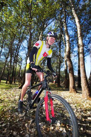 panning shot: Panning shot di una mountain bike, corse in una foresta. Macchina fotografica panoramica - movimento su sfondo. Alcuni del corpo e del viso in focus.