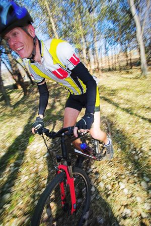 panning: Panning shot of a mountain biker, racing in a forest. Panning:  movement on background and some of the bike and biker.  Focus on body of the racer.