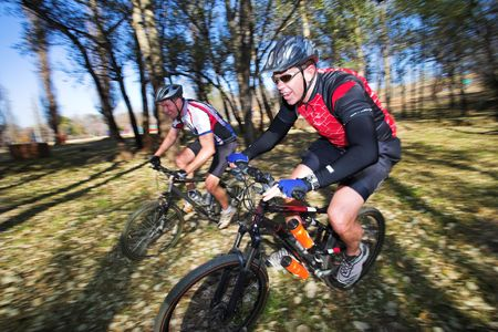 panning shot: Panning shot of two mountain bikers, racing in a forest.  Movement, some of the bikers in focus.