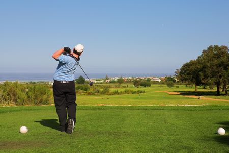 A golfer playing golf on a green.  Movement on golf club and ball in the air. photo