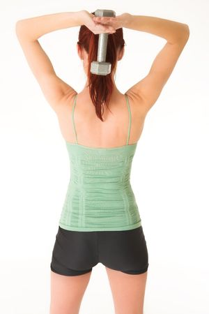 A woman in gym clothes, holding a weight behind her back. Stock Photo - 466033