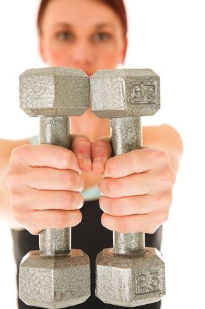 A woman in gym clothes, holding weights out in front of her.  Shallow DOF – face out of focus, weights and hands in focus. Stock Photo - 466030