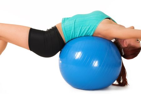 A woman in gym clothes, laying on her back on a Pilates ball Stock Photo - 466041