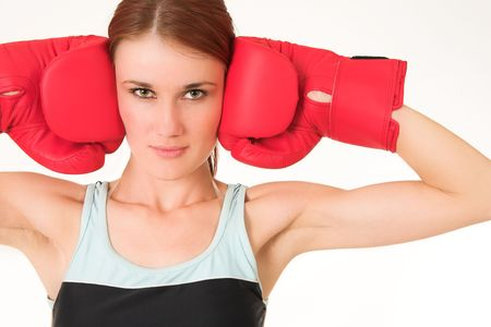 A woman in gym clothes, wearing red boxing gloves. photo