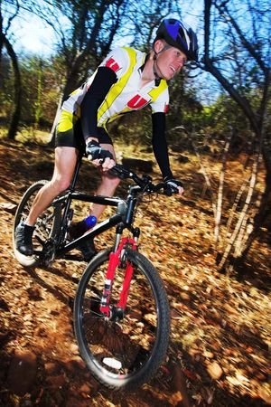 Panning shot of a mountain biker, racing in a forest.  Movement on background and some of the bike.  Face of biker in focus. Stock Photo