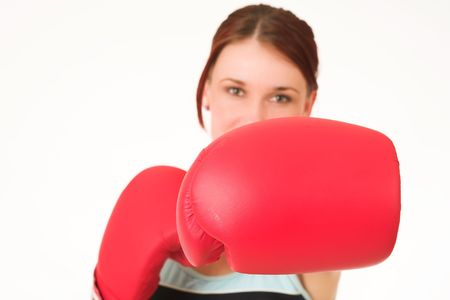 A woman in gym clothes, with boxing gloves.  Shallow D.O.F. - woman out of focus, boxing gloves in focus. Stock Photo - 488223