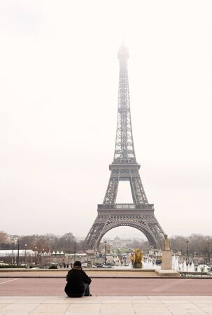 A person sitting, looking at the Eiffel Tower in Paris, France.  Copy space. photo