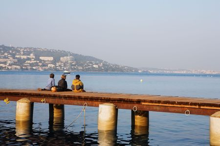 Three kids fishing from the pier on Ile Sante-Marguerite – Cannes in Background, France Stock Photo - 488141