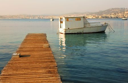 Old fishing boat next to the pier of Ile Sante-Marguerite � Cannes in Background, France photo