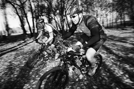 panning shot: Filtraggio del colpo di due bikers della montagna, corrente in una foresta. Movimento, alcuni dei bikers nel fuoco. Archivio Fotografico