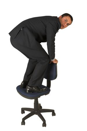 grand strand: Businessman wearing a suit and a grey shirt.  Standing  on an office chair. Stock Photo