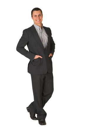 grand strand: Businessman wearing a suit and a grey shirt.  Standing  with both hands in his pockets, smiling. Stock Photo