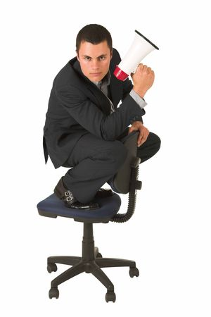 Businessman wearing a suit and a grey shirt.  Making a stunt on an office chair with a megaphone in his hand. photo