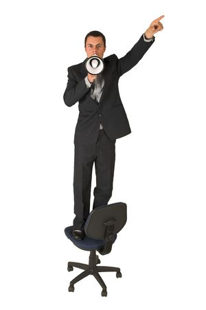 grand strand: Businessman wearing a suit and a grey shirt.  Making a stunt on an office chair with a megaphone in his hand, pointing upwards with his other hand. Stock Photo