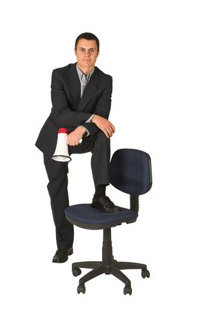 grand strand: Businessman wearing a suit and a grey shirt.  Making a stunt on an office chair with a megaphone in his hand. Stock Photo