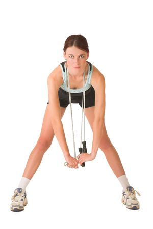 bending over: Woman in gym wear bending over with skipping rope around her neck. Stock Photo