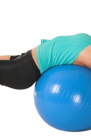 Woman in gym wear laying on her back on blue ball. photo